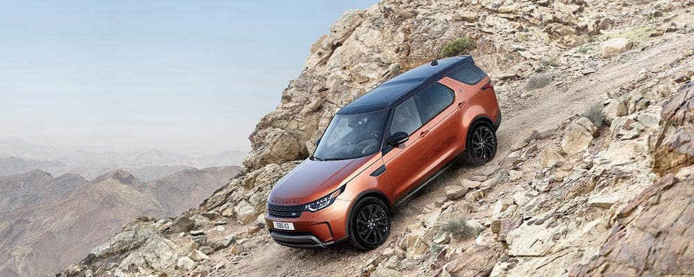 Orange Land Rover Discovery driving down a steep, rocky mountain