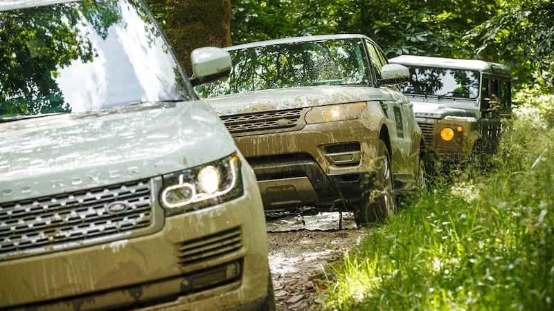 Line of Land Rover models off-roading through mud