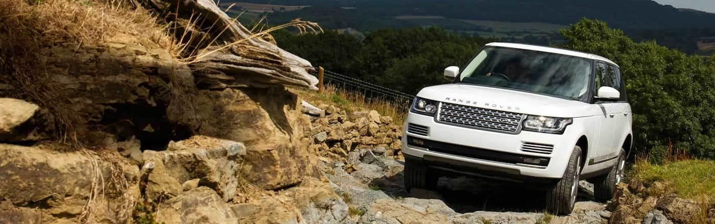 White Land Rover driving up rocky hill
