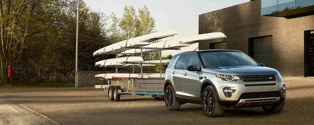 silver 2019 land rover discovery sport towing a rack of boats