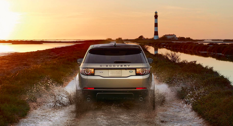Rear view of Silver Discovery Sport driving through a marsh