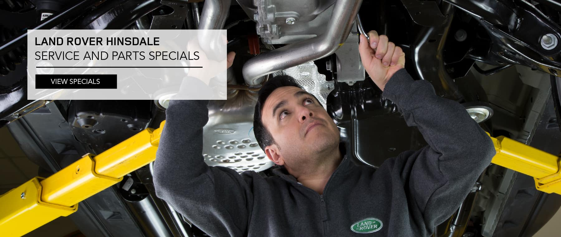 LAND ROVER HINSDALE SERVICE AND PARTS SPECIALS. VIEW SPECAILS. SERVICE TECHNICIAN PERFORMING MAINTENANCE UNDERNEATH A CAR.