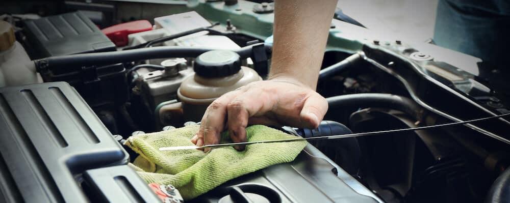 mechanic checking oil dipstick