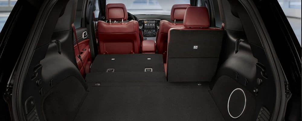 2019 jeep grand cherokee interior view of cargo area with rear seat partially down and red leather interior