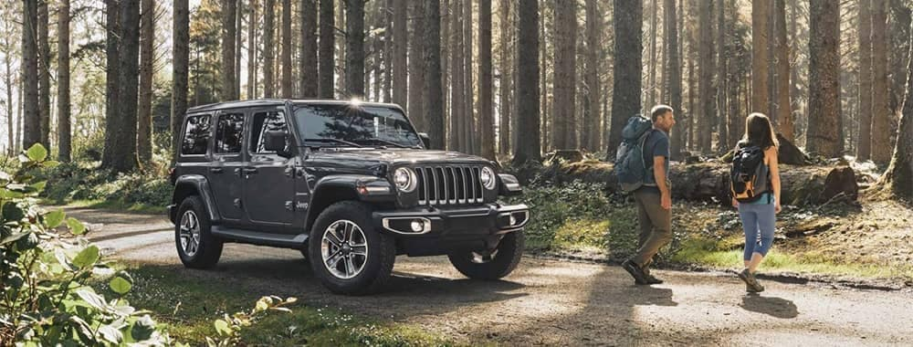 Jeep Wrangler Parked in Forest with Couple Hiking