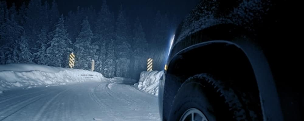 Car driving at night on a snowy road