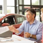 couple signing documents at car dealership
