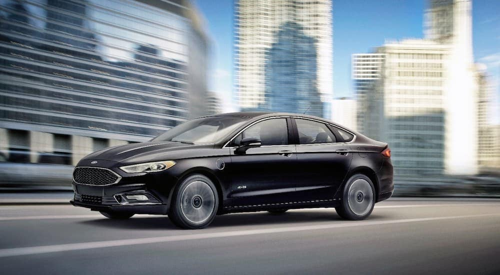 A black 2017 Ford Fusion is driving past city buildings.