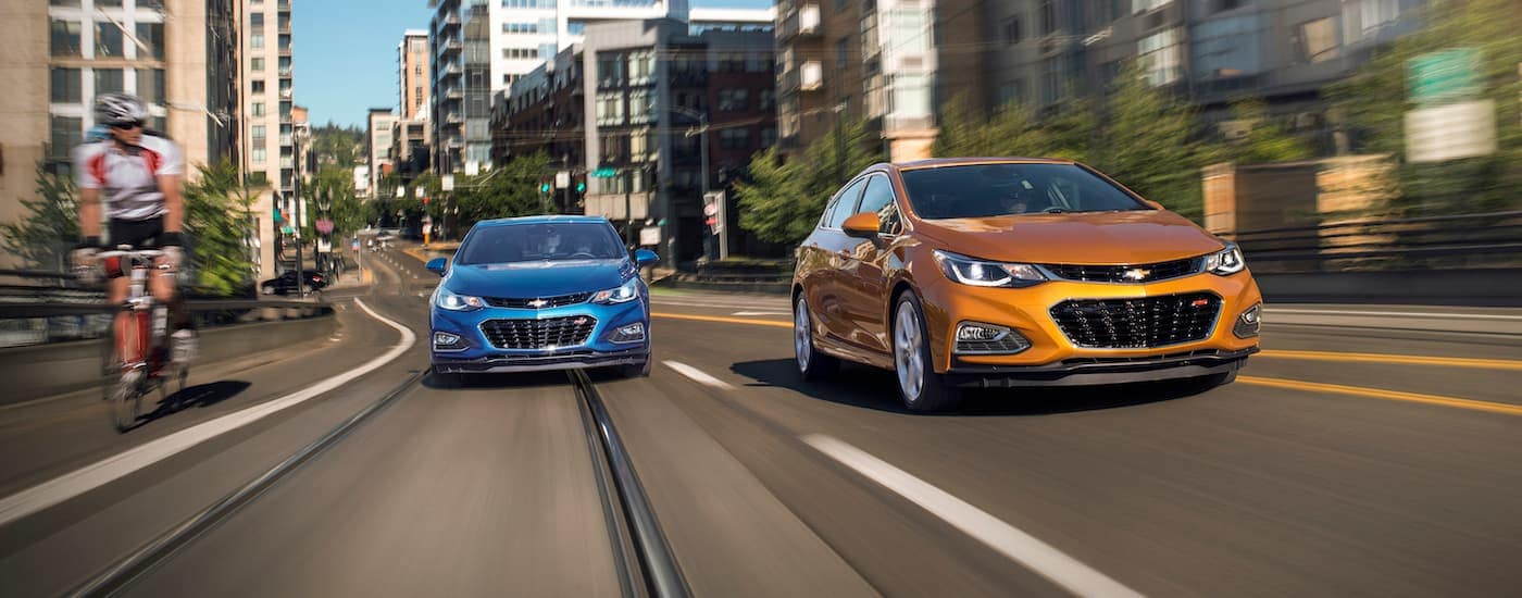A blue and an orange 2017 Chevy Cruze are driving down a city street.