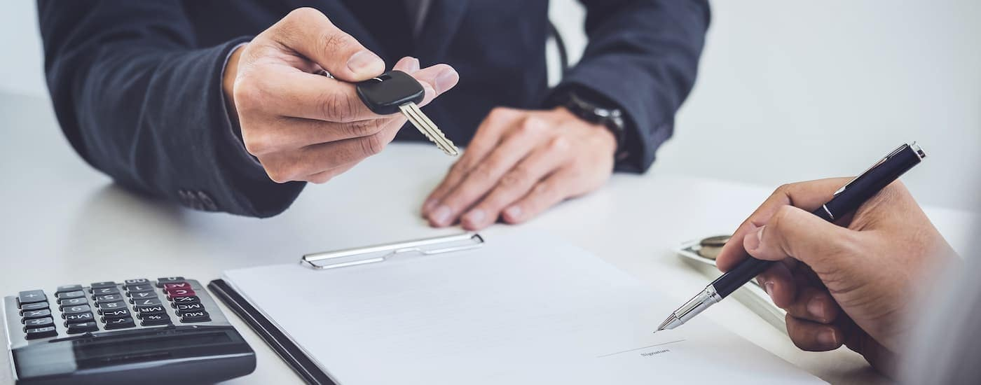 A closeup is shown of a salesman's hands giving keys to a buyer signing paperwork.