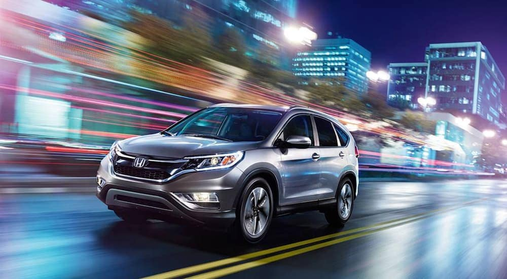 A silver 2016 Honda CR-V, one of the popular used SUVs for sale in Philadelphia, PA, is driving past city building at night.