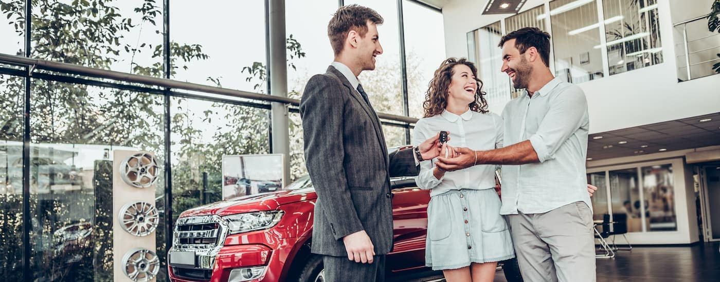 A happy couple is buying a red SUV at a dealership.
