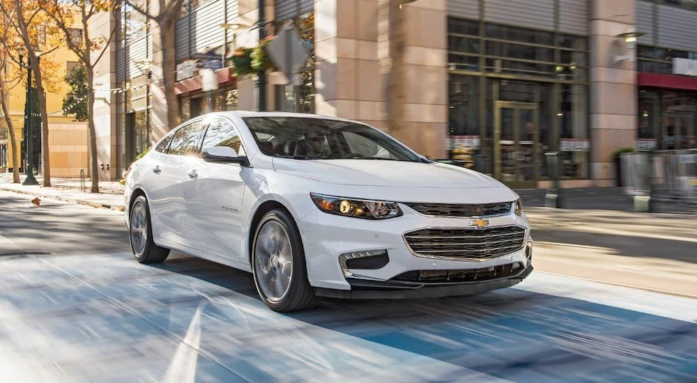 A white 2016 Chevy Malibu, frequently purchased when it comes to used cars near me, is driving through an intersection.