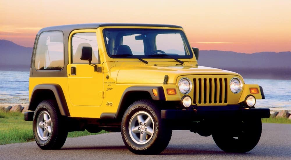 A yellow 2001 Jeep Wrangler sport, popular among used SUVs for sale, is parked in front of a bay at sunset.