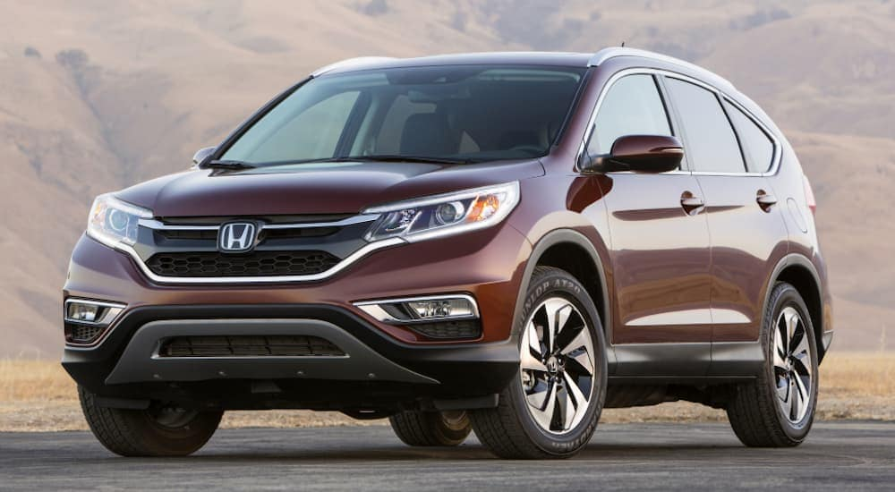 A burgundy 2016 Honda CR-V is parked with hills in the distance.