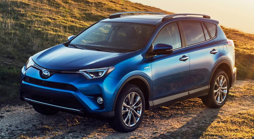 A blue 2016 Toyota RAV4 is parked on a dirt road at sunset near Philadelphia, PA.
