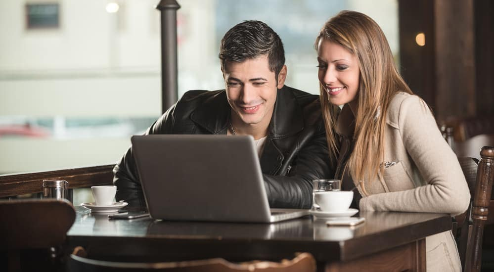 A couple is researching used cars near them on a laptop in a Philadelphia, PA cafe.