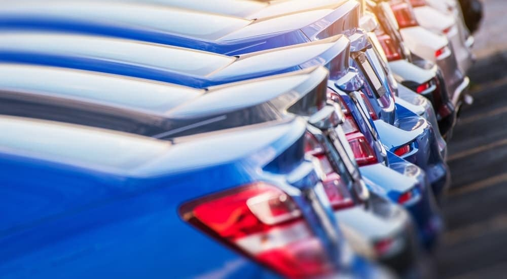 A line of blue and black cars are shown from their trunks at a dealership for used cars near me.