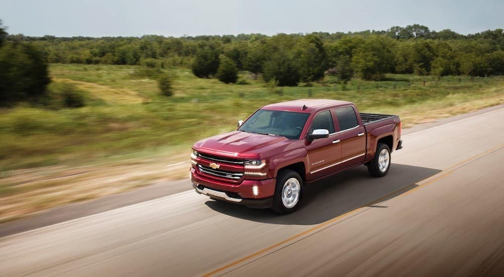 A red 2017 Chevy Silverado is driving on a highway.