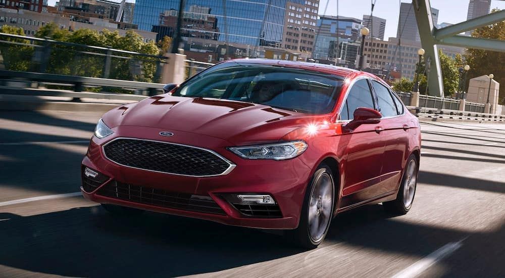 A red 2017 Ford Fusion is driving over a bridge near Philadelphia, PA.