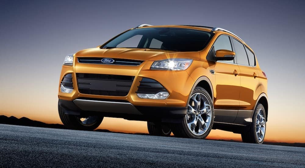 A yellow 2016 Ford Escape, which is popular among used cars for sale, is parked at sunset.
