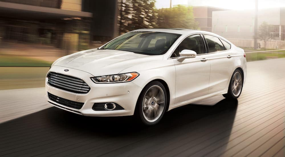 A white 2013 Ford Fusion, popular among used cars for sale, is driving on a city street near Philadelphia, PA.
