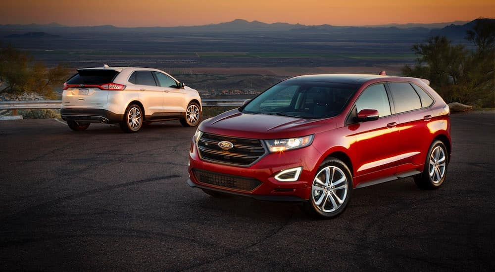 A red 2015 Ford Edge is parked in front of a white one at sunset.
