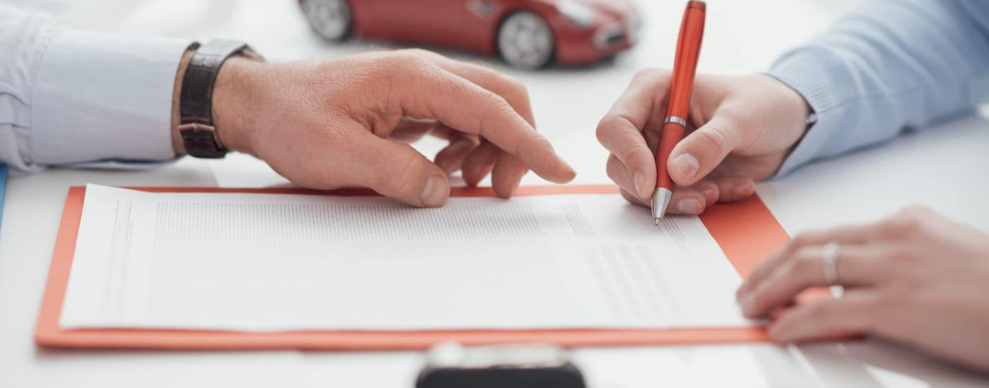 A close up is shown of a buyer signing a car loan while the seller points.