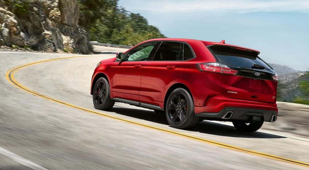A red 2019 Ford Edge ST is driving around a corner going uphill.