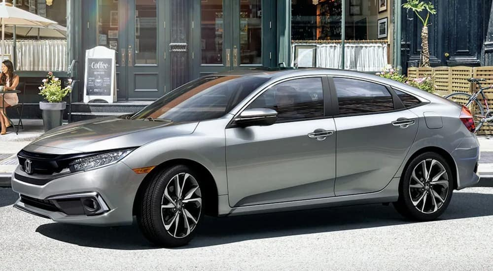 A silver 2019 Honda Civic, which is popular among used cars in Philadelphia, PA, is backing into a parking spot on the street.