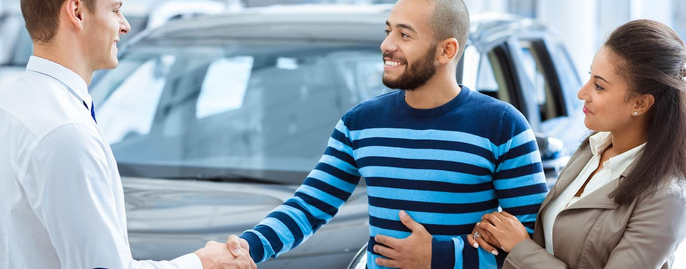 A husband is shaking the hand of a car salesman at a dealership.