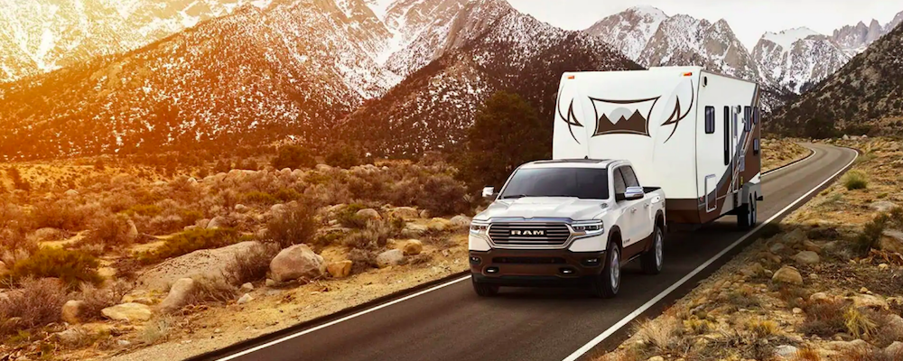 White 2019 RAM 1500 Towing Trailer in Mountains at Sunset