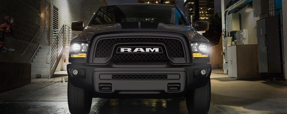 Front of black 2019 RAM 1500 in alley at night with headlights on