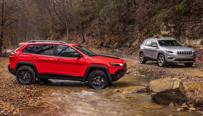 Red 2019 Jeep Cherokee Trailhawk and Silver 2019 Jeep Cherokee Limited at creek