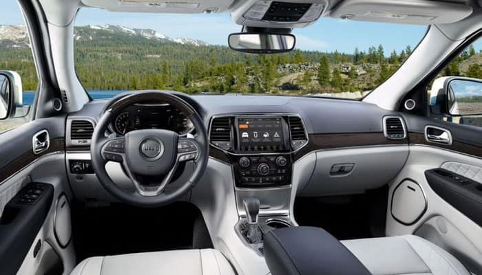 2019 Jeep Grand Cherokee interior with white seats looking at forest mountains