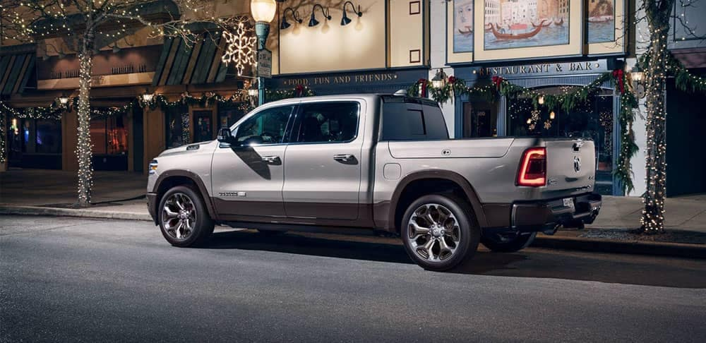 Off-white 2020 Ram 1500 Laramie Longhorn parked downtown near Christmas lights