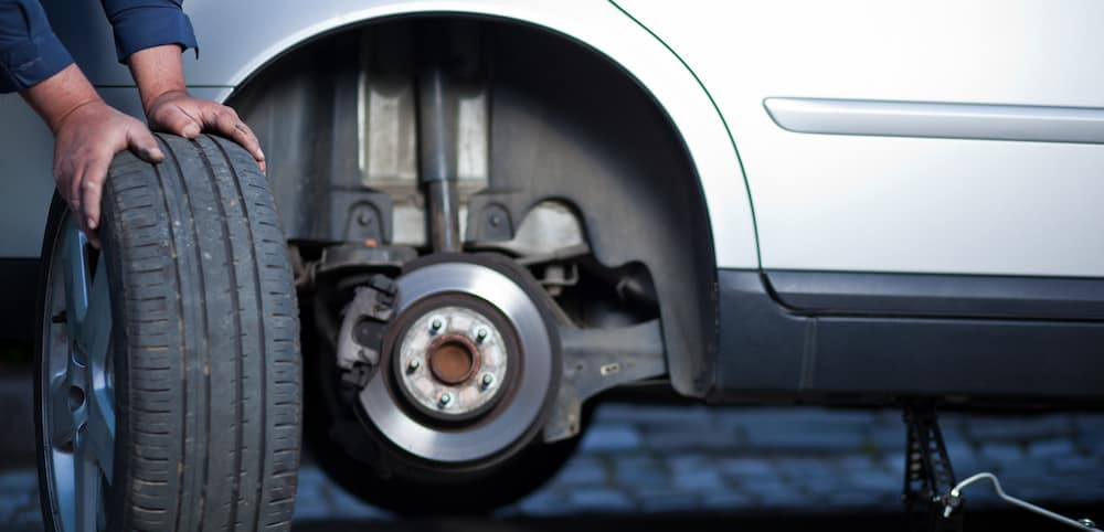 Unseen mechanic with tire doing tire rotation on white car