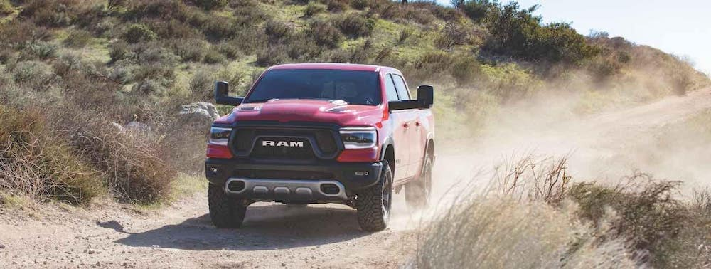 Red 2020 RAm 1500 kicking up dust as it drives in the desert