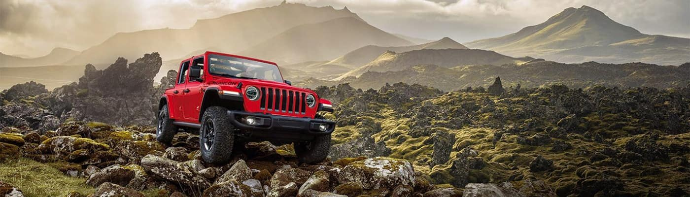Jeep Wrangler Parked on Rocky Ground with Mountains in Background
