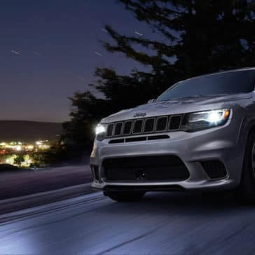 2018 Jeep Grand Cherokee driving at nighttime through snow