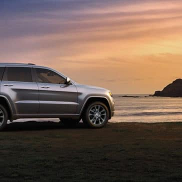 2018 Jeep Grand Cherokee parked on a beach at sunset