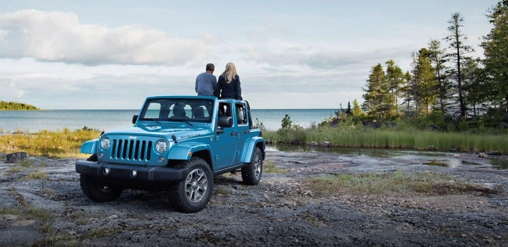 Two people standing in the back of a 2018 Jeep Wrangler JK parked at a rocky beach