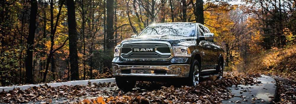 2018 Ram 1500 driving through a tree lined road in fall