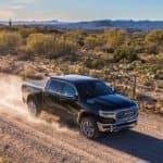 2019 RAM 1500 pickup truck driving down gravel road