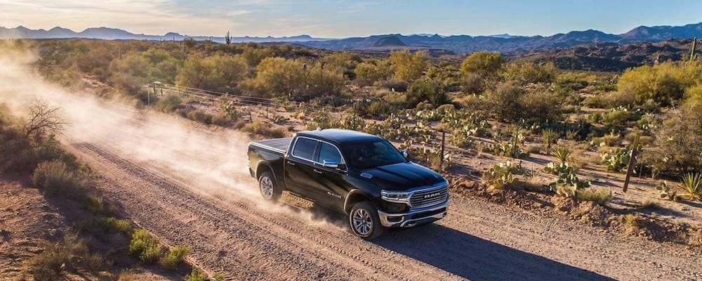 2019 RAM 1500 pickup truck driving down gravel road