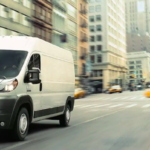 White Promaster Van driving in city with skyscrapers
