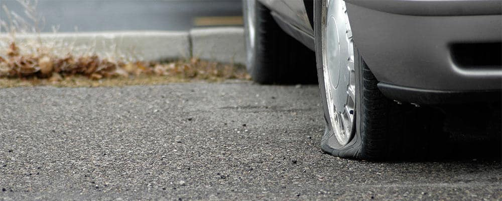 close up of a flat tire in a parking lot