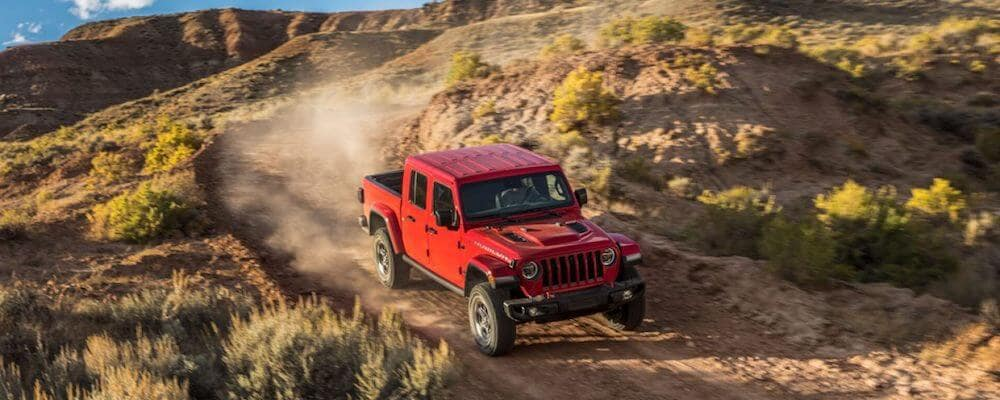 red jeep gladiator driving on desert road