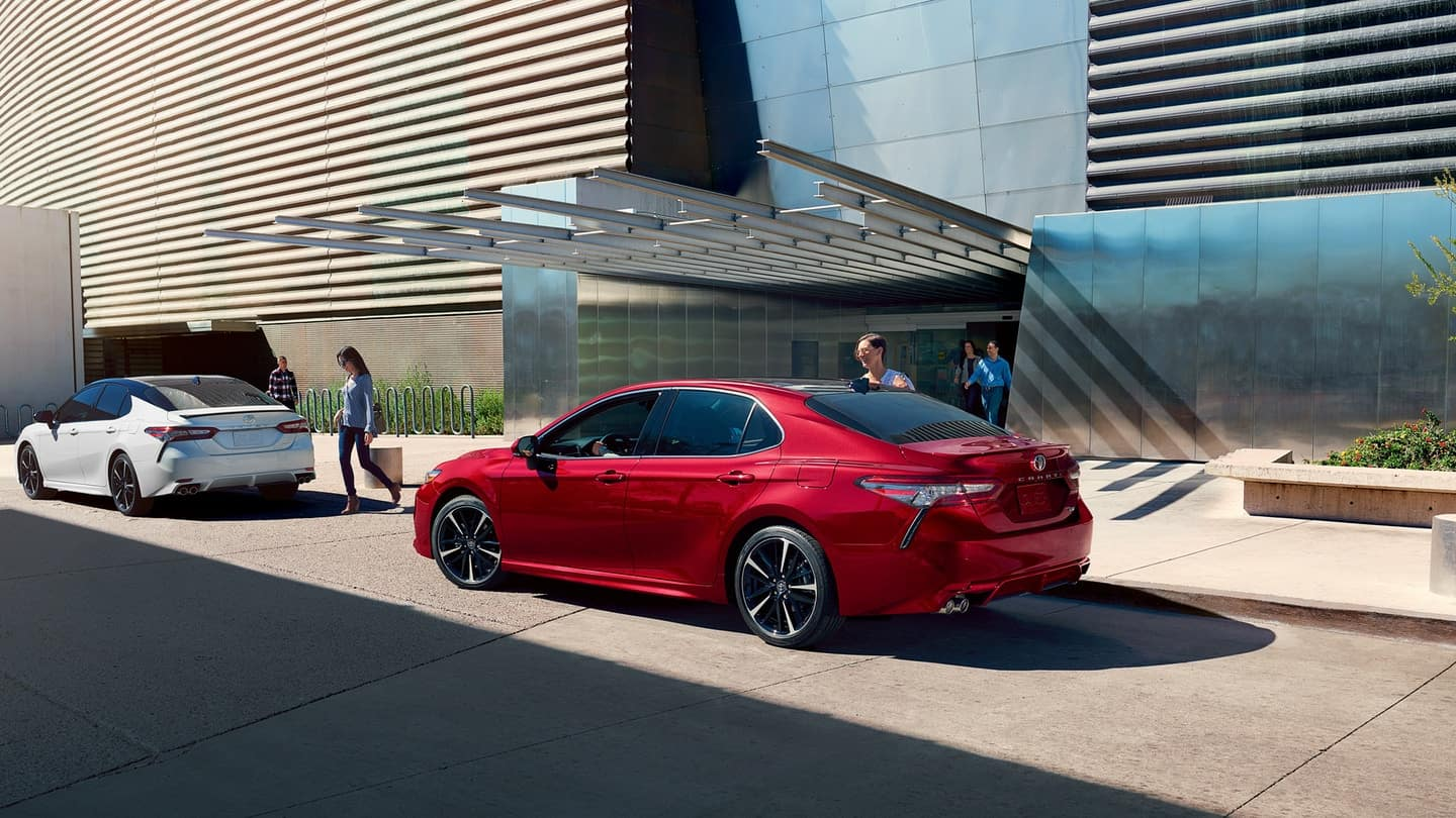 Image of a red 2019 Toyota Camry parked outside a metal and glass building.