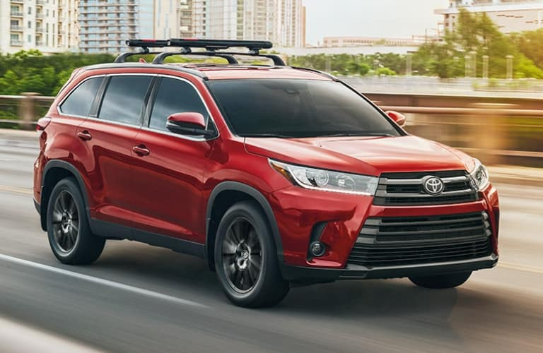 Image of a red 2019 Toyota Highlander SUV driving.